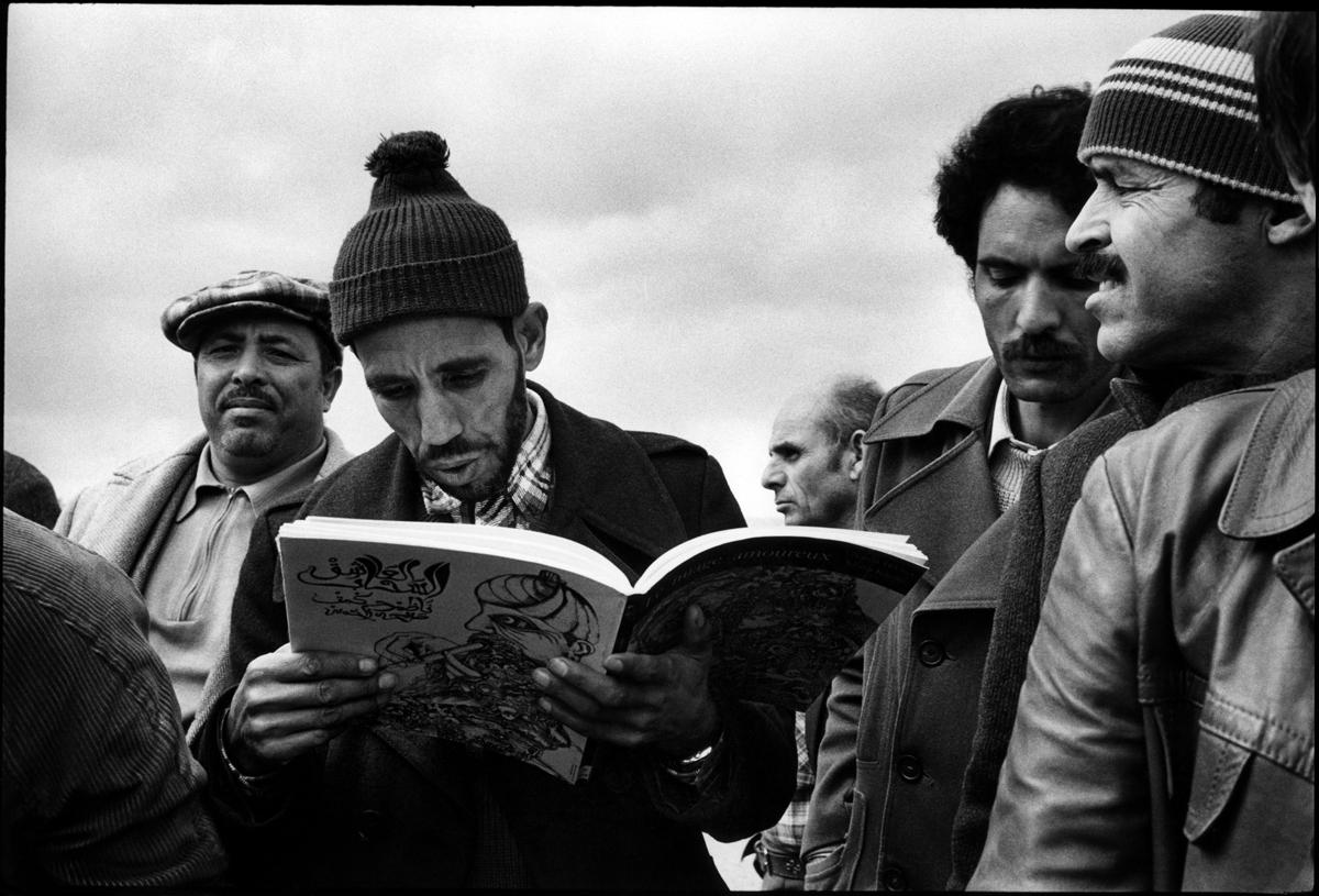 """Citroën Aulnay, la première grève. 1982.. La bibliothèque de la ville vient de mettre ˆ la disposition des grèŽvistes une table de livres. Un ouvrier lit """"le nuage amoureux"""" du poète turc Nazim Hikmet."""